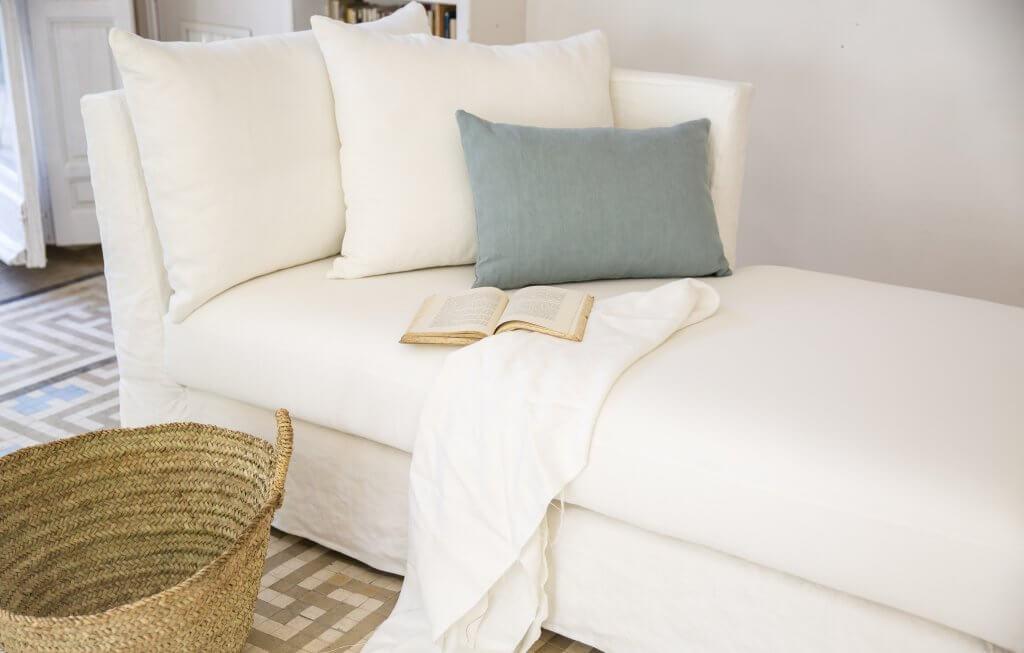 Chaise longue de lino blanco con cojines y plaid de cama también en lino